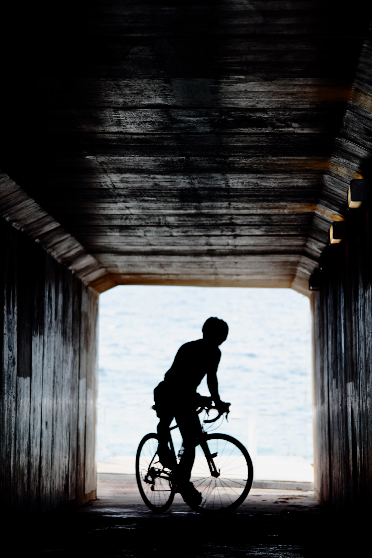 Cyclist in a tunnel silhouetted against the sea